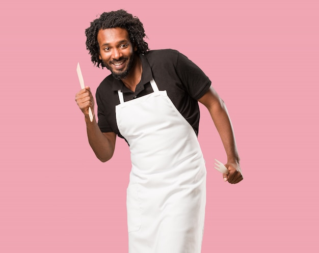 Handsome african american baker listening to music, dancing and having fun