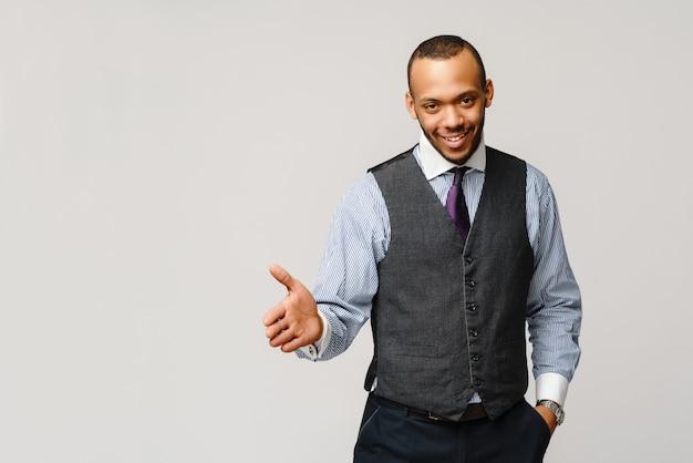 Красивый афро-американский бизнесмен рукопожатие жест светло-серая стена.