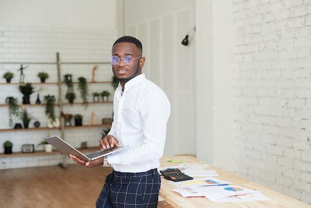 Красивый афро-американский бизнесмен в рубашке и классических брюках использует ноутбук и смотрит в камеру, улыбаясь во время работы в офисе.
