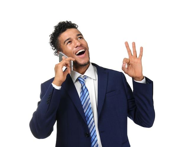 白の携帯電話で話しているハンサムなアフリカ系アメリカ人のビジネスマン
