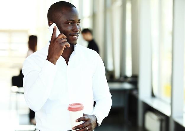 現代のオフィスで携帯電話で話しているハンサムなアフリカ系アメリカ人のビジネスマン