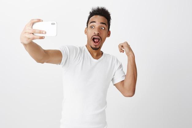 잘 생긴 아프리카 계 미국인 남자가 셀카를 위해 팔뚝을 구부리고 소셜 네트워크 추종자에게 근육을 보여줍니다.