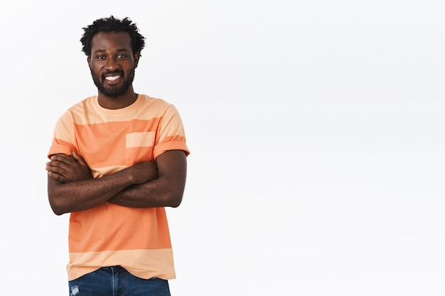 Handsome african american guy with afro haircut standing in casual t-shirt