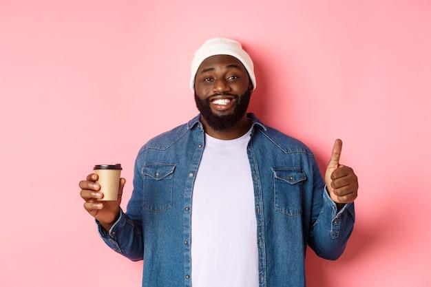 Красивый афро-американский битник мужчина показывает палец вверх, пьет кофе и рекомендует кафе, стоя на розовом фоне.