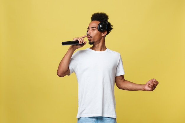 Handsome african american male singer performing with microphone.