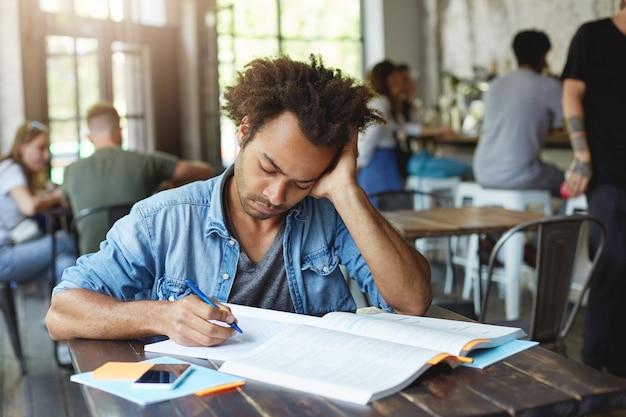 잘 생긴 아프리카 계 미국인 남성 학생은 숙제를 다시해야하고, 과제에 집중하고, 실수 한 곳을 찾으려고, 집중된 표정으로 카피 북을 쳐다 보며 피곤하고 스트레스를받습니다.