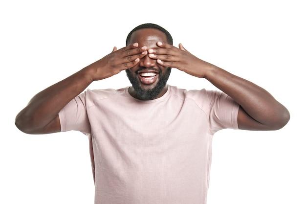 白い背景に目を覆っているハンサムなアフリカ系アメリカ人の男