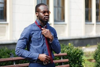 Handsome African American man fixes his red tie on blue shirt standing outside