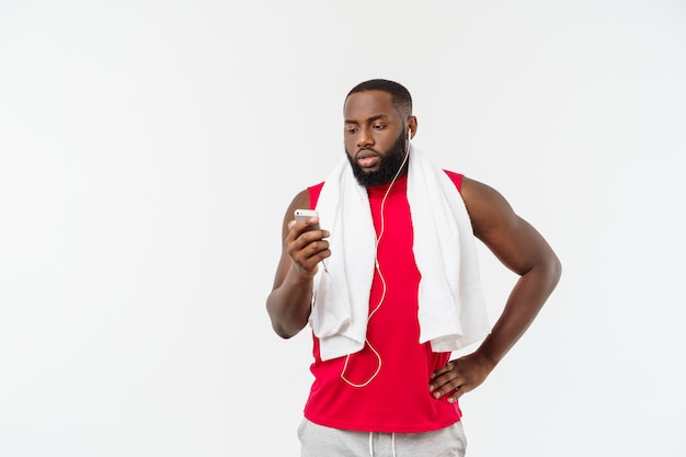 Handsome african american man listening music on his mobile device after sport exercise.