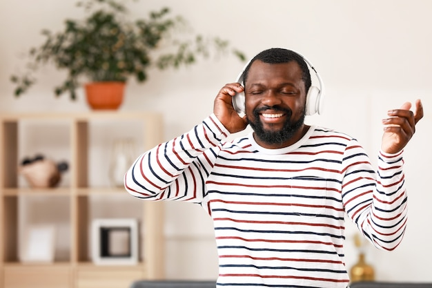 Handsome african-american man listening to music at home