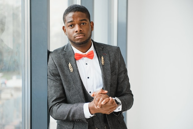 Красивый афро-американский мужчина возле окна в офисе