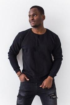 잘 생긴 아프리카 계 미국인 남자는 흰색 바탕에 검은 셔츠에 포즈. 청소년 스트리트 패션