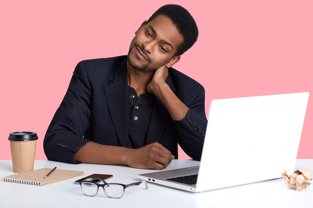 Handsome african american man sitting at desk, wearing classic jacket, looking very tired, putting his hands on his neck, feels pain, looks aside and tries to relax, working online, uses wi fe.