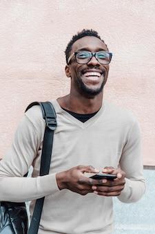 Красивый афро-американский мужчина, улыбаясь с смартфон