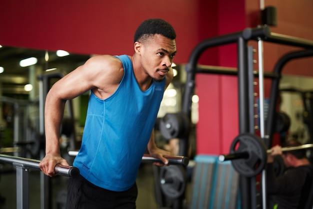 ハンサムなアフリカ系アメリカ人男性のジムでトレーニング
