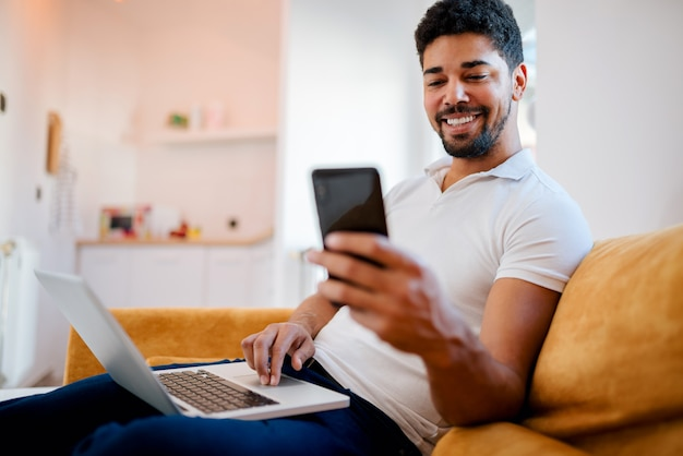 Handsome african american man using laptop and mobile phone at home.