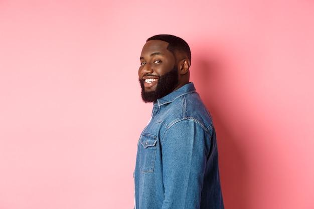Bell'uomo afroamericano con la barba, gira la faccia alla telecamera e sorride fiducioso, in piedi su sfondo rosa