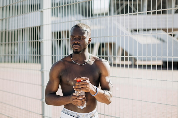 Handsome african american man with naked chest poses with a bottle of water