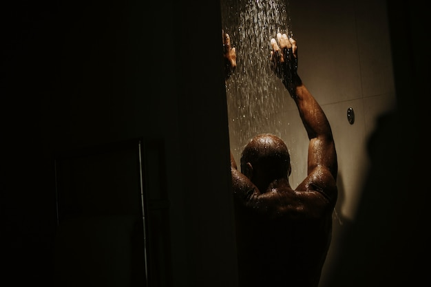 Handsome african american man with naked torso takes shower