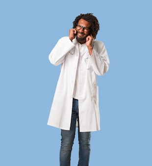 Handsome african american medical doctor covering ears with hands