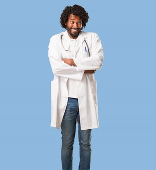 Handsome african american medical doctor doubting and shrugging shoulders