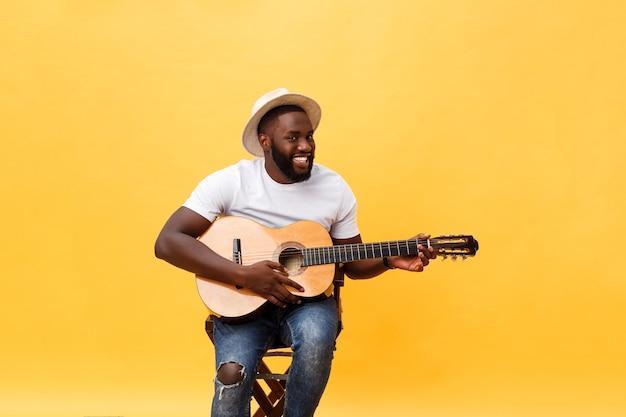 Красивый афро-американский гитарист в стиле ретро играет на акустической гитаре