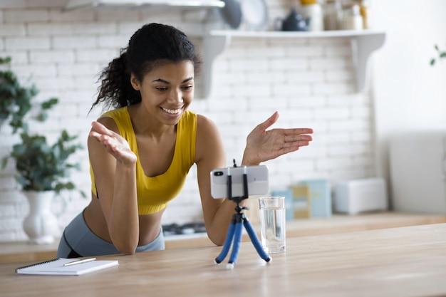 ハンサムなアフリカ系アメリカ人女性のフィットネスvloggerは、自宅のキッチンでフィットネスと健康的なライフスタイルについてのストリーミングビデオを記録し、若い女性ブロガーはスマートフォンでソーシャルメディアのvlogを撮影します
