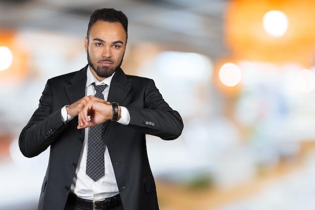 Красивый афро-американский молодой человек, глядя на часы. копировать пространство