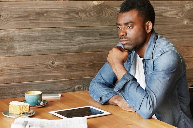 思いやりのある表情のデニムジャケットを着たハンサムなアフリカのブロガー。マグカップ、ケーキ、新聞、空白の画面のタッチパッドのあるコーヒーショップのテーブルに座って、新しいポストを考えながらあごに触れます。
