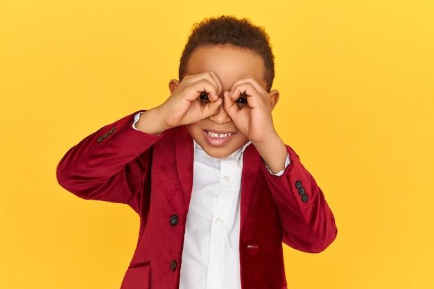 遠くを見ている双眼鏡を使って何かを調べているハンサムなアフリカの少年。双眼鏡を使って誰かをスパイしている好奇心旺盛なスヌーピーの暗い肌の子供。