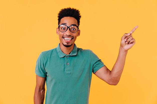 驚きを表現する大きな眼鏡をかけたハンサムなアフリカの少年。黒い巻き毛の感情的な男性モデルの屋内ショット。