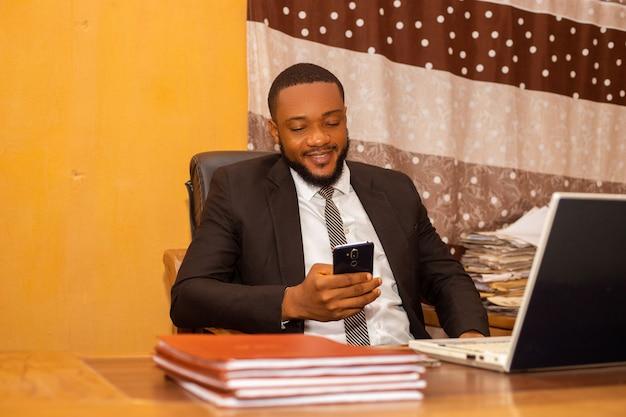 사무실에서 휴대폰을 들여다보는 잘생긴 아프리카 사업가