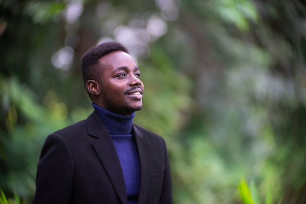 Handsome african business man in trendy formal black suit. guy with beard wearing blue long sleeve or sweater