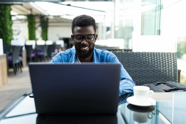 カフェでラップトップでオンライン会議を持ち、コーヒー、パノラマ、コピースペースを飲むハンサムなアフリカのビジネスマン