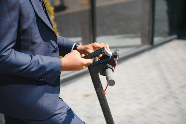 Красивый африканский бизнесмен, езда на электрическом скутере на открытом воздухе