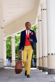 Handsome african businessman walking with cell phone