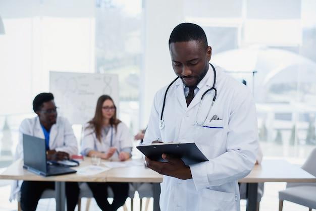 Красивый африканский доктор в белом халате делает некоторые заметки. молодой студент-медик с стетоскопом вокруг его шеи держит папку.