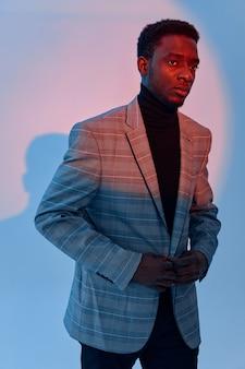 スーツの自信のネオンの背景にハンサムなアフリカの男。高品質の写真