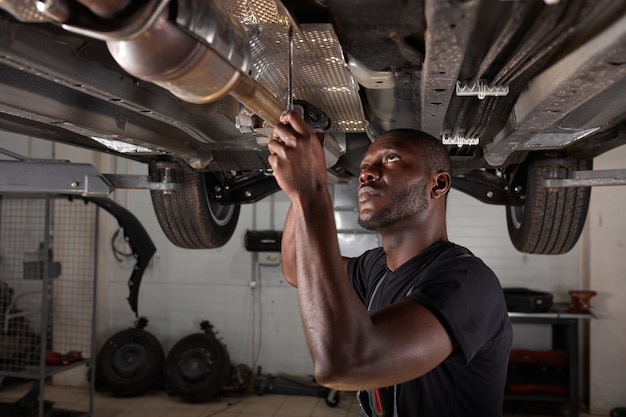 Handsome african male repairing bottom of car