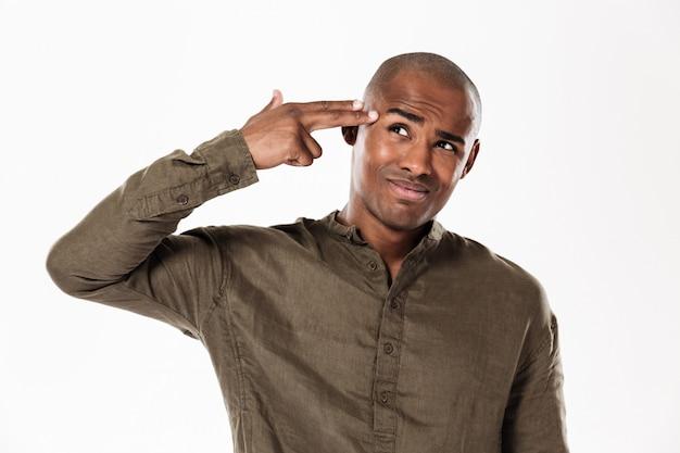 Красивый африканский человек держа руку в жесте пистолета около головы и смотря прочь