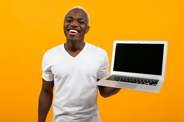 Handsome african man holding laptop computer with mockup on yellow