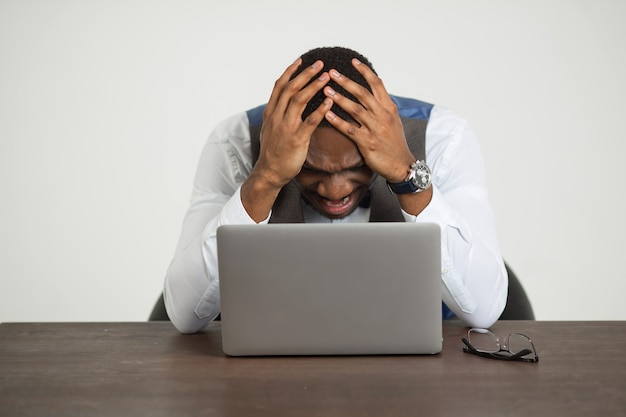 양복에 잘 생긴 아프리카 남자는 흰 벽에 노트북과 함께 테이블에 앉아