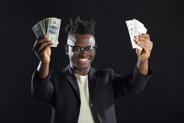 Красивый африканский мужчина в костюме с долларами в руках