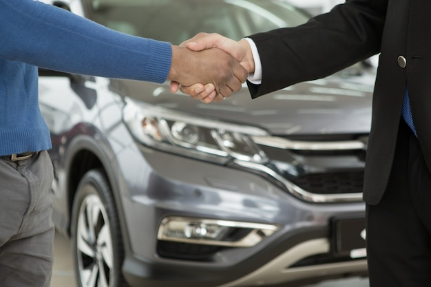 Handsome african man shaking hands with car dealer after buying an auto