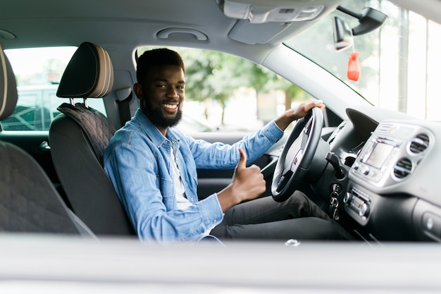Handsome african man show thumbs up inside car
