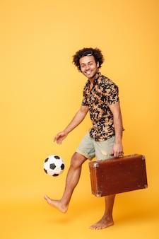 ハンサムなアフリカ人立っているとスーツケースとサッカーを保持