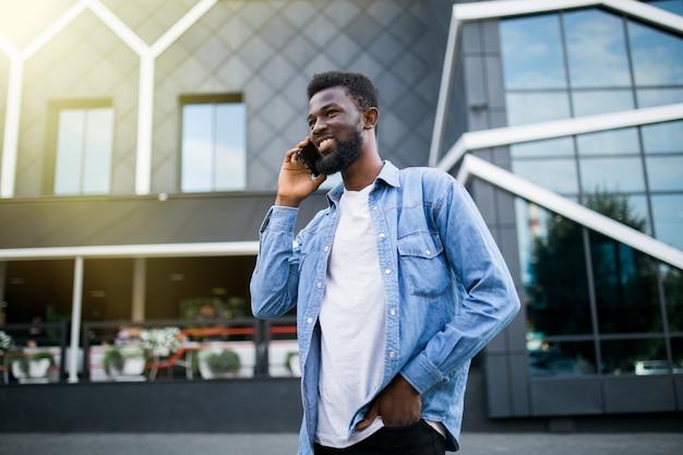 公園で電話で話しているハンサムなアフリカ人。