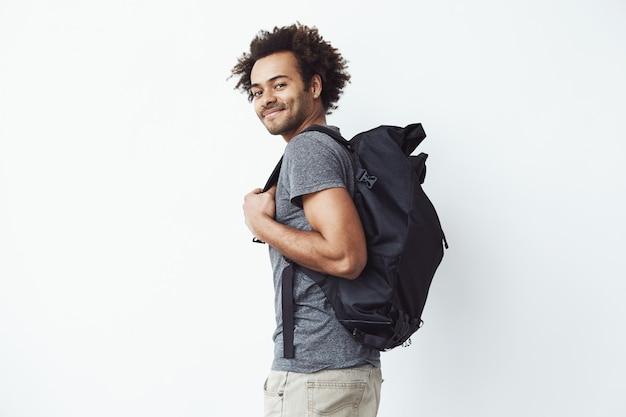 プロファイルに立っている笑顔のバックパックでハンサムなアフリカ人。