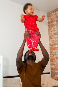 Handsome african man with dreadlocks with little daughter at home