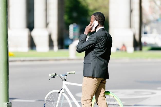 휴대 전화 및 고정 된 기어 자전거 거리에서 잘 생긴 아프리카 남자.